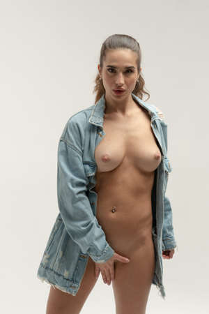young beautiful woman posing nude in the studio, standing in a blue denim jacket