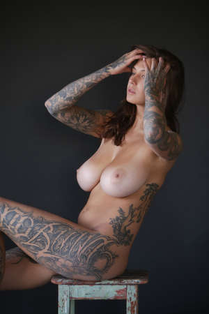 young beautiful woman with tattoo pose in studio