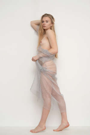 young beautiful woman posing nude, standing in a transparent dress
