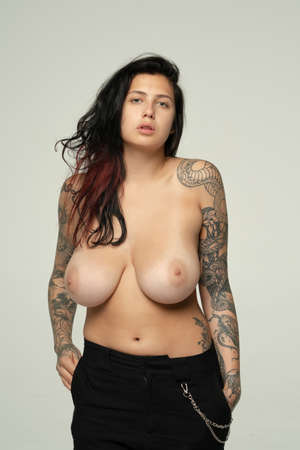 young beautiful woman with tattoo posing nude in studio Banque d'images