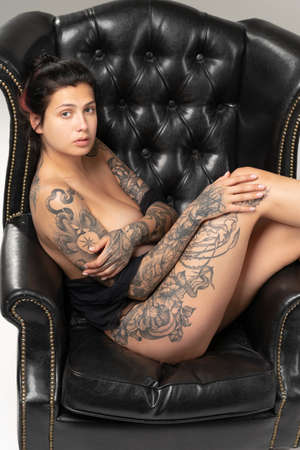 young beautiful woman with tattoo pose nude in studio