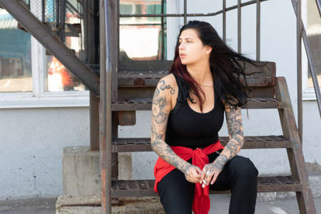 young beautiful woman with tattoo sits on the steps outside and smokes Banque d'images
