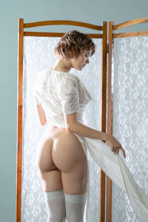 young beautiful woman positions in the studio, stands in white stockings