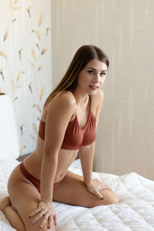 young beautiful woman pose in the studio, sitting in brown lingerie on the bed Banque d'images