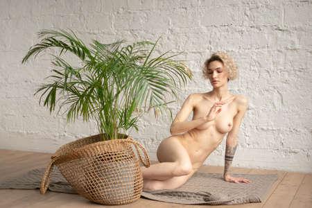 young beautiful woman posing nude in the studio, sitting on the floor Standard-Bild
