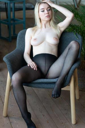 young beautiful woman pose in black pantyhose in the studio