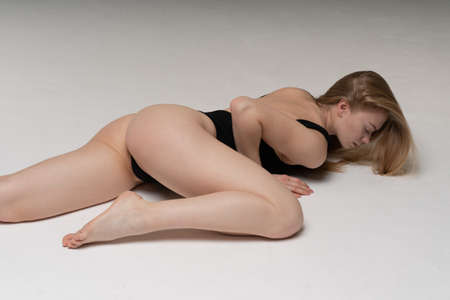 young beautiful girl pose in a black bodysuit in the studio, sitting on the floor