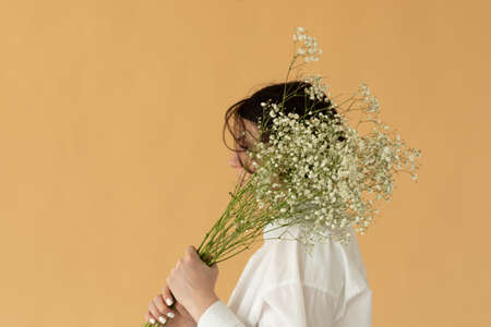 portrait of a girl in the studio in a white shirt with white flowers 版權商用圖片
