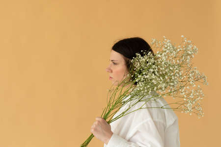 portrait of a girl in the studio in a white shirt with white flowers Фото со стока