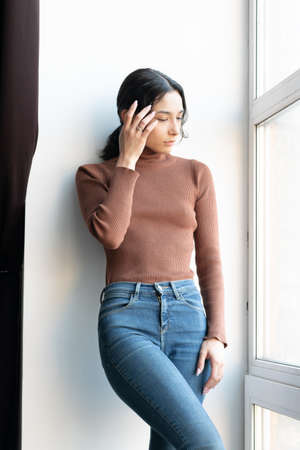 young beautiful woman stands in blue jeans near the window