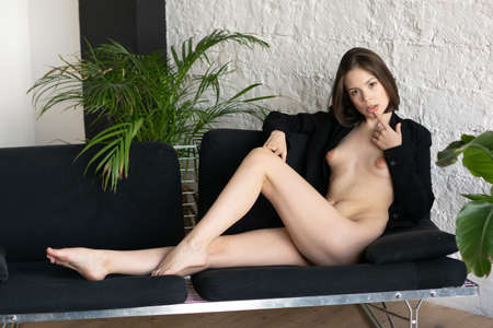 young beautiful woman posing nude in the studio, sitting on the bed