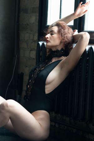 young beautiful woman pose in black bodysuit in the studio, sitting on the floor