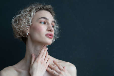 portrait of a woman in the studio near a black wall Фото со стока