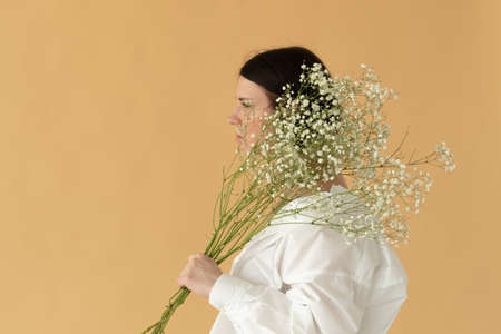 portrait of a young beautiful woman in the studio with white flowers on a yellow background Фото со стока