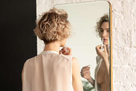 young beautiful woman paints lips near the mirror