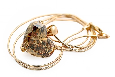 A gold locket with heart shape champagne diamond on a chain. Shallow depth of field - focus on the locket.  photo
