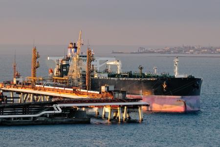 cami�n cisterna: La carga de aceite en un superpetrolero en el terminal petrolero Foto de archivo