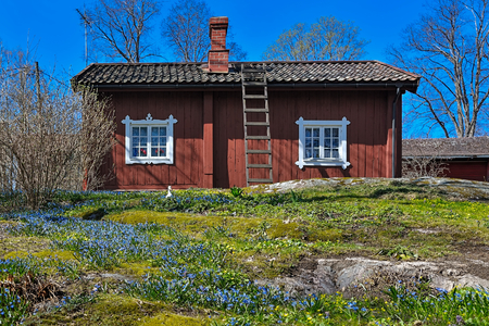 ironworks: Traditional red ochre painted wooden house at Fagervik Ironworks works street, Finland. Most of the surviving huts date to the beginning of the 19th century. Stock Photo