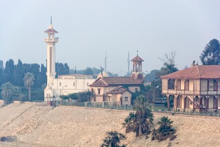 sinai peninsula: Mosque and church on Suez canal coast foggy morning