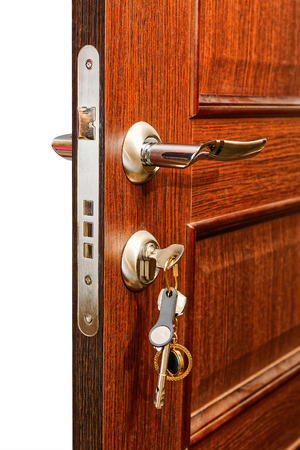 door handle: Slightly opened wooden door with group of modern keys on keychain as a concept for home ownership or for security and door policy privacy Stock Photo