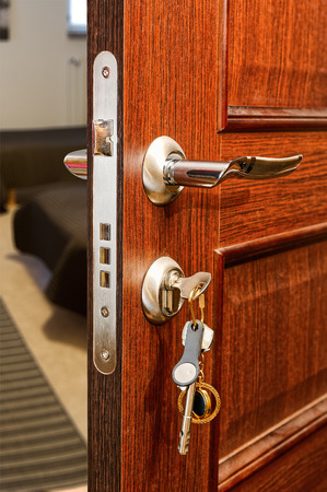 Slightly opened wooden door with group of modern keys on keychain as a concept for home ownership or for security and door policy privacy Stock Photo