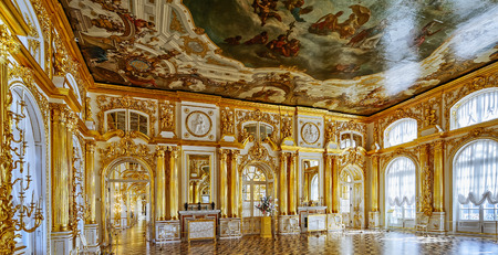 pushkin: Ornate interior of the Catherine Palace with gilded details, large mirrors and windows. Tsarskoe Selo (Pushkin), St. Petersburg, Russia.