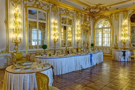 tiled stove: Decorated tables with the badges and sashes of Russian orders of chivalry in Chevaliers? Dining Room of Catherine Palace banquet room in Tsarskoe Selo (Pushkin), St. Petersburg, Russia. In the corner is a multi-tiered tiled stove with cobalt painting, col