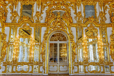 Ornate interior of the Catherine Palace with gilded details, large mirrors and windows. Tsarskoe Selo (Pushkin), St. Petersburg, Russia.