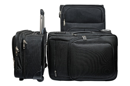 Set of three matching black suitcases of different sizes with telescoping metal handles and wheels made from a black ballistic nylon photo