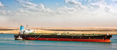 Tugboat tugs help turn around a large oil tanker. Egypt Suez canal northbound Stok Fotoğraf
