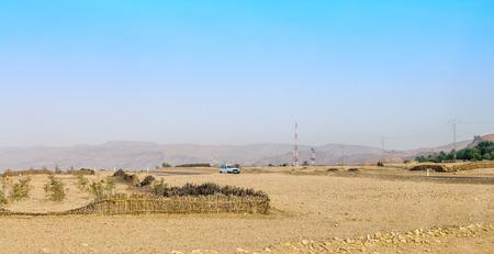 desierto del sahara: El camino a lo largo de la frontera del desierto del Sahara con las monta�as del Atlas en el fondo