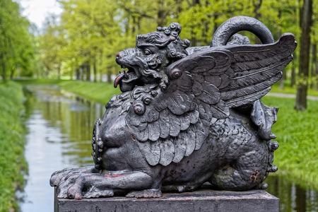 drago alato: Statua di bronzo antico del drago cinese alato sul ponte al parco