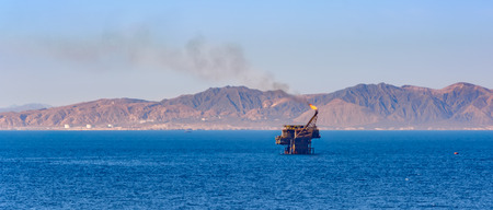 persian gulf: Offshore oil rig with flame on background of  Persian Gulf Coast Stock Photo