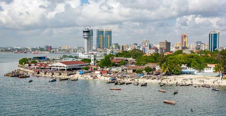 pescador: Barcos de pescadores frente a mercado de pescado Kivukoni con la torre de control y Puerto Rascacielos Detrás, Dar Es Salaam, Tanzania Foto de archivo
