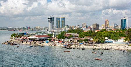 Fisherman boats in front of Kivukoni fish market with Port control tower and Skyscrapers Behind, Dar Es Salaam, Tanzania Stockfoto