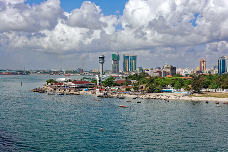 ポート コントロール タワーと高層ビルの後ろ、ダルエスサラーム、タンザニア キブコニ フィッシュ マーケットの前に漁師船 写真素材