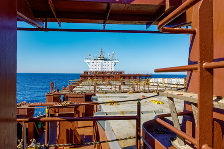 Empty upper deck of container ship. View from the bow on deckhouse with navigation bridge under blue sky.