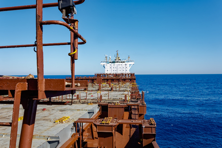 ship bow: Empty upper deck of container ship. View from the bow on deckhouse with navigation bridge under blue sky.