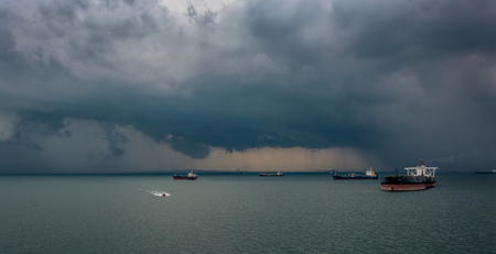 passing over: Tropical rain storm passing over ships, South China Sea, Singapore, Malaysia
