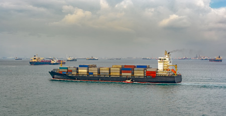 delivers: Pilot boat delivers a pilot on container ship coming from the harbor into the sea