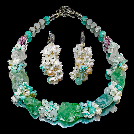 mirro: Close-up view to handmade earrings and necklace with a large fluorite, quartz, faceted glass beads, agate, freshwater pearls and small flowers from foamiran (artificial suede), similar to the flowers of lilac. Some flowers toned in pale green. Black mirro