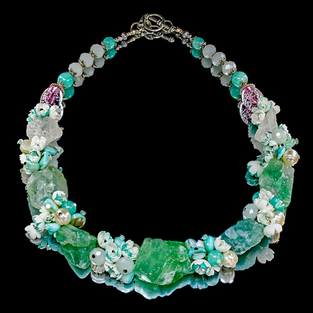 freshwater pearl: Close-up view to handmade necklace with a large fluorite, quartz, faceted glass beads, agate, freshwater pearls and small flowers from foamiran (artificial suede), similar to the flowers of lilac. Some flowers toned in pale green. Black mirror background