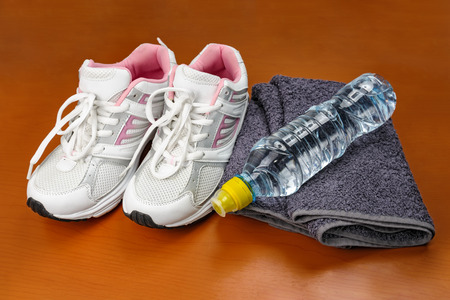 untied: A pair of new girl sport indoor shoes with towel and bottle of water at wooden surface as concept of healthy lifestyle