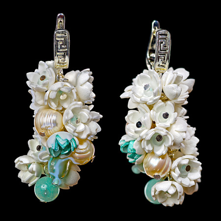 freshwater pearl: Close-up view to handmade earrings with a freshwater pearls, agate, nacre and small flowers from foamiran (artificial suede), similar to the flowers of lilac. Some flowers toned in pale green. Stock Photo