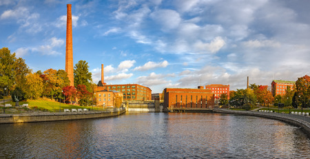 Fall colors and old factory building of red brick on embankments channel of rapids Tammerkoski. Tampere, Finland Stock Photo