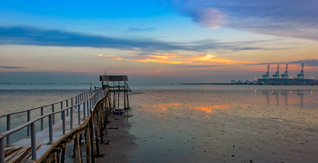 guard rail: Long wooden jetty for fisherman boats, stretching into the sea at low tide Stock Photo