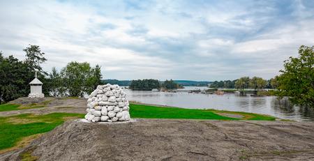 navigation mark: White stone cairn and modern navigation mark on lake shore