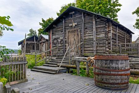 cabaña: Rústicos antiguos graneros de madera con paseo marítimo frente a ellos Foto de archivo