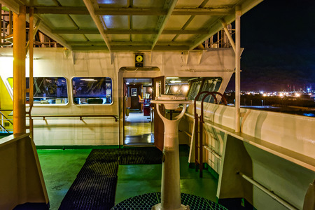freighter: Wing bridge deck of a freighter ship with navigational equipment at rainy night