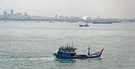 commercial fishing net: Commercial fishing trawler boat in front of Singapore